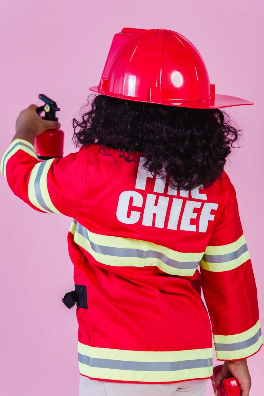 anonymous ethnic kid in fireman costume in studio