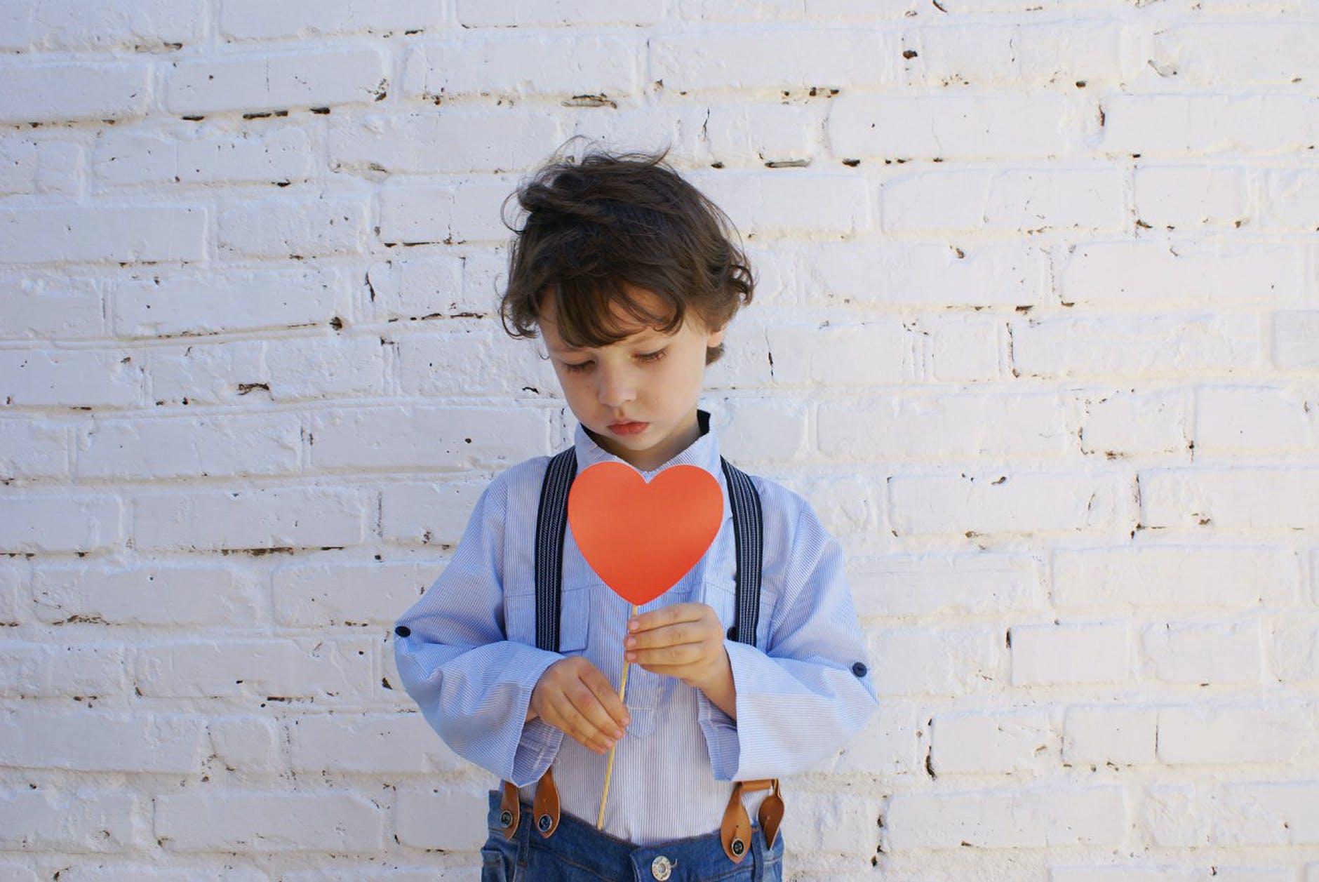 photo of boy holding heart shape paper on stick