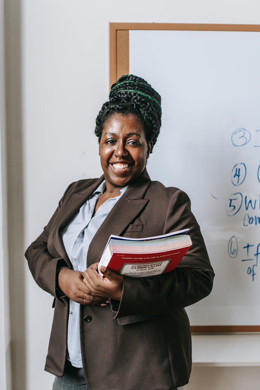 happy black female teacher standing with workbooks near whiteboard