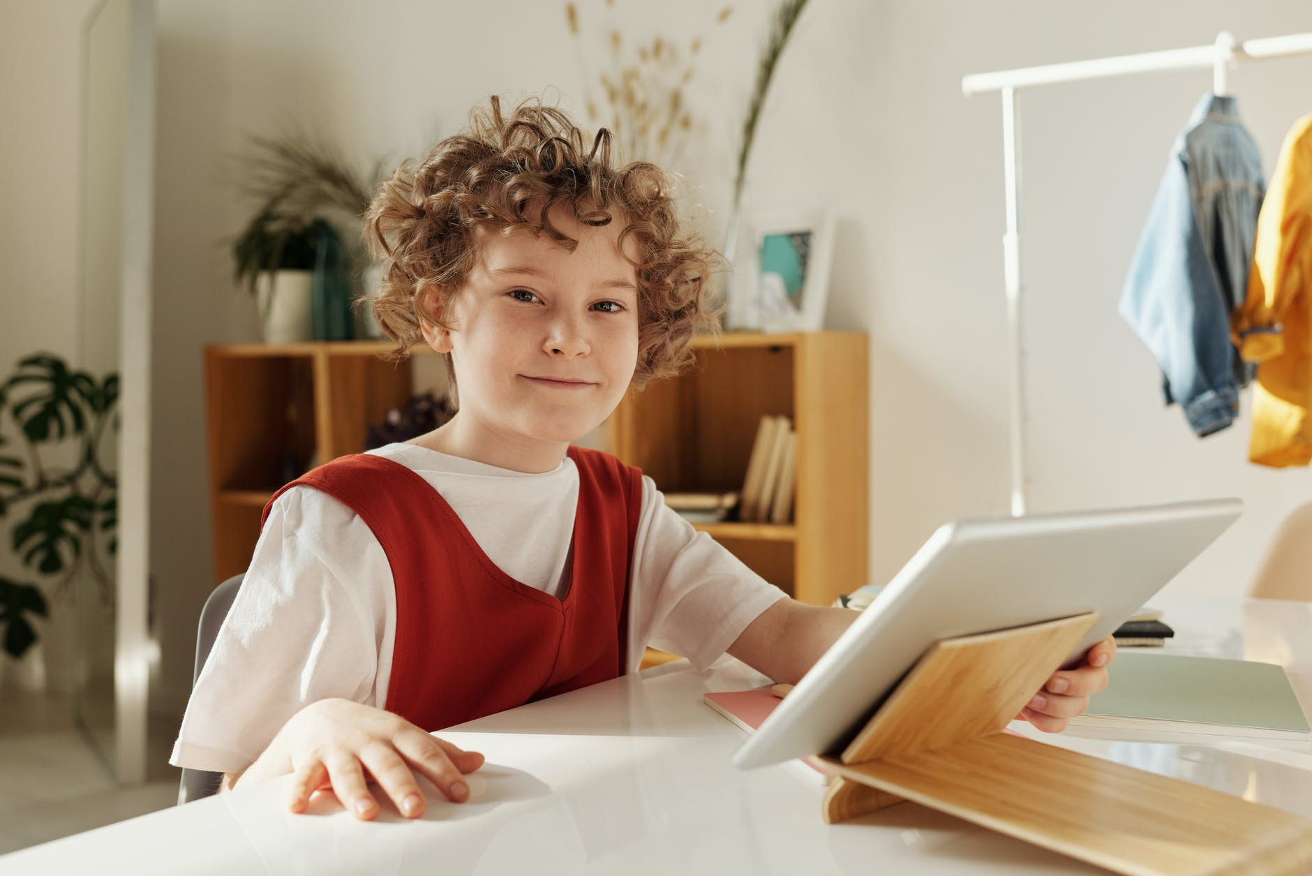 child smiling while holding silver tablet